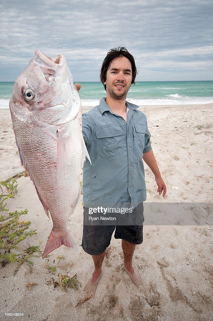 Man holding snapper caught from beach : Stock Photo