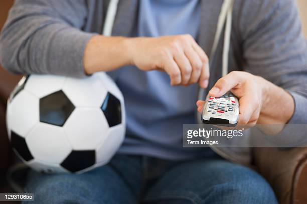 Man holding soccer ball and remote control