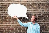 Man holding speech bubble beside brick wall