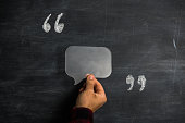 Hand holding speech bubble between quotation marks hand written with chalk on blackboard