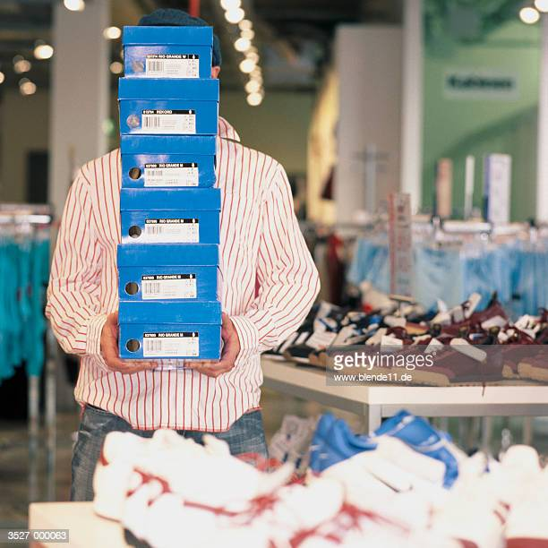 Man Holding Stack of Shoeboxes