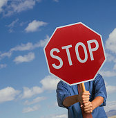 Man holding stop sign in front of face