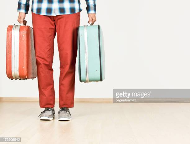 Man holding suitcases, indoors
