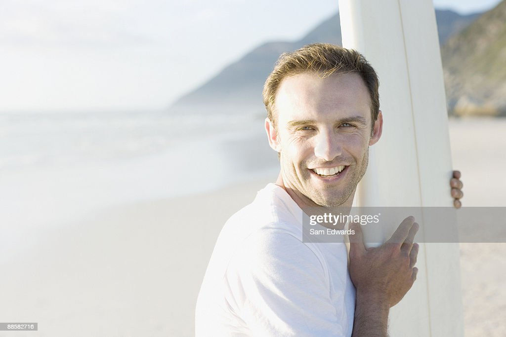 Man holding surfboard at beach : Stock Photo