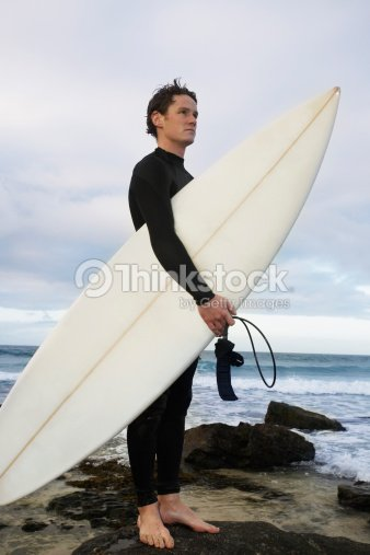 man holding surfboard on rocks on beach side view ストックフォト