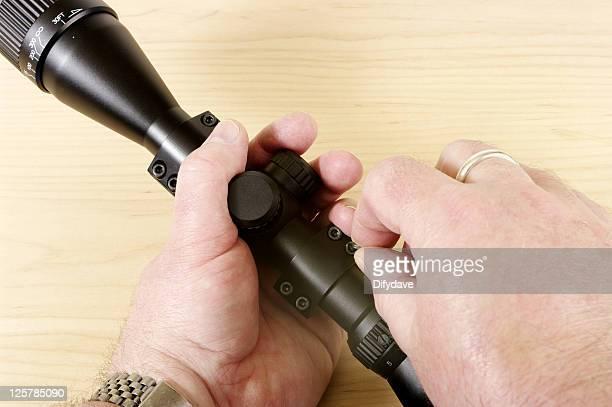 Man Holding Telescopic Rifle Sight Undoing Mounts