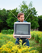 Man holding television in field