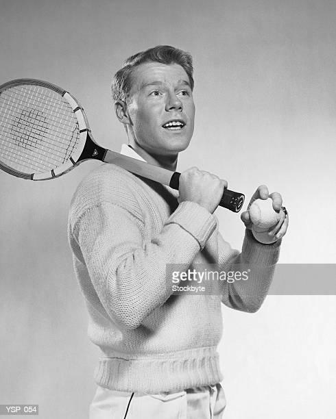 Homme tenant la raquette de tennis-dessus son épaule