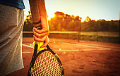 Close up of man holding tennis racket on clay court. In his hand is tennis ball. On court is sunset.