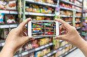 man holding the smart phone, using the Augmented Reality buy some food in the supermarket