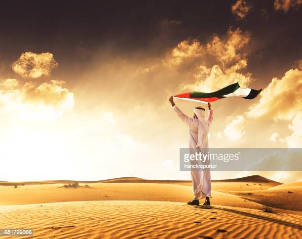 man holding the uae flag in the desert