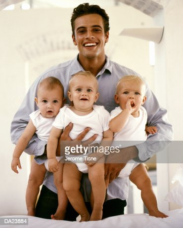 Man holding three babies (3-6 months) high section : Stock Photo