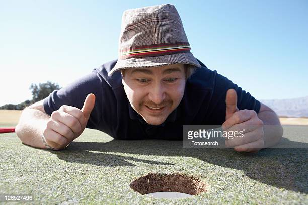 Man holding thumbs up by golf hole