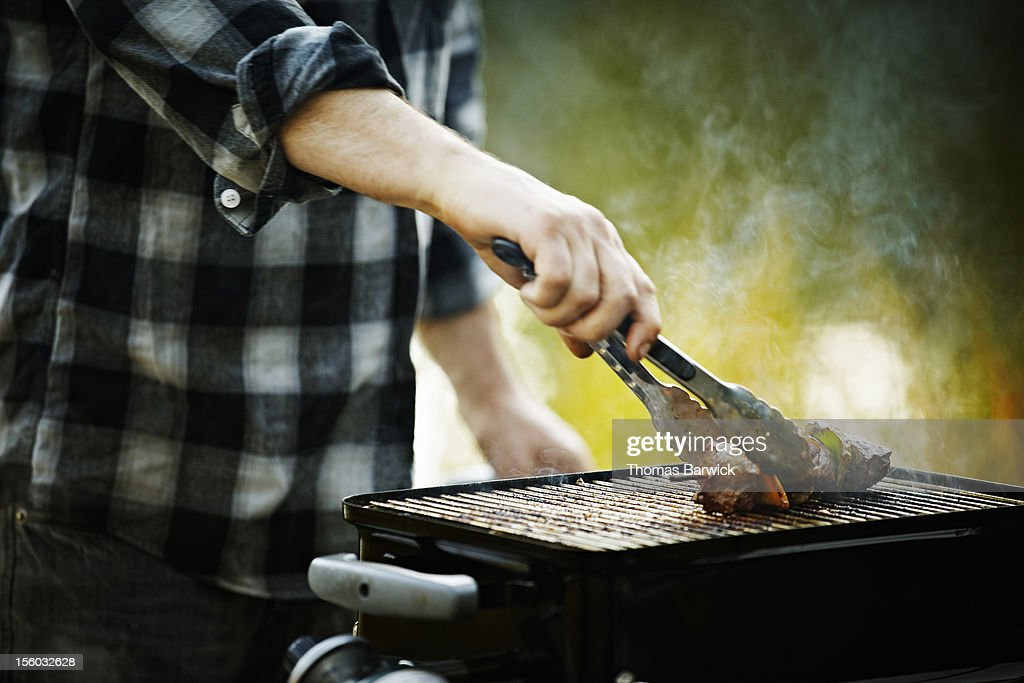 Man holding tongs barbecuing kebab on grill