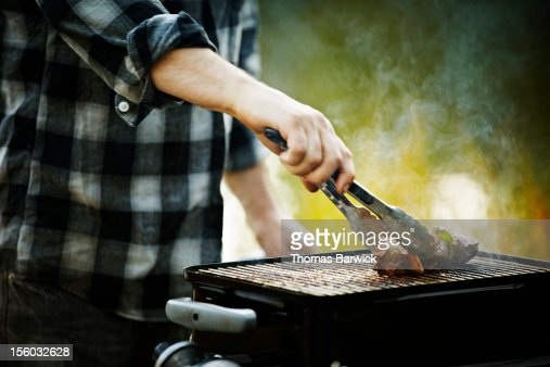 Man holding tongs barbecuing kebab on grill : Photo