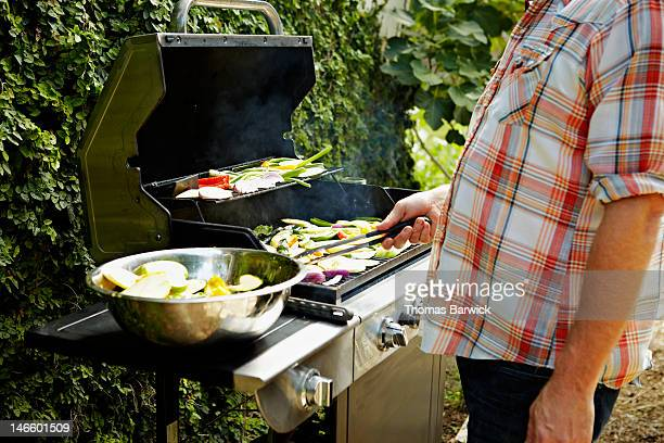 Man holding tongs barbecuing vegetables at grill