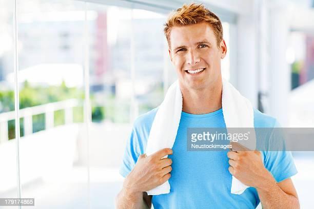 Man Holding Towel Around Neck In Gym