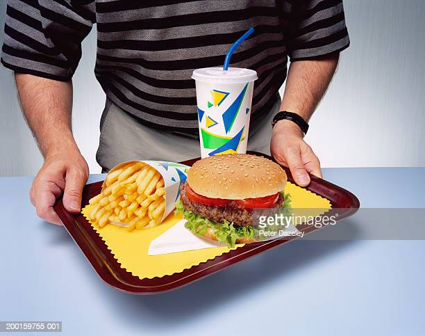 Man holding tray with fast food meal, close-up