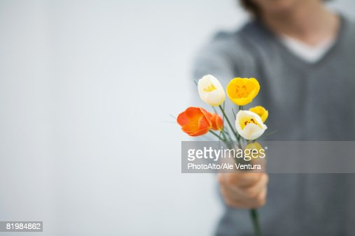 Man holding tulips out toward camera, cropped view, focus on foreground