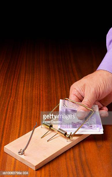 Man holding twenty pound notes in mouse trap, close-up