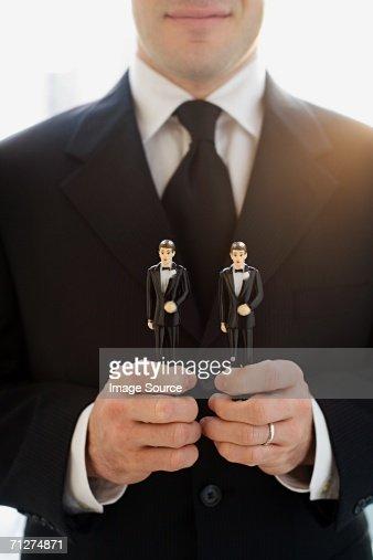 Man holding two groom wedding cake figurines