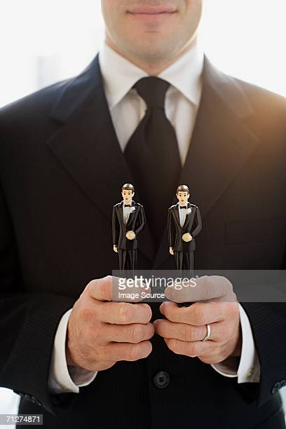 Man holding two groom wedding cake figurines