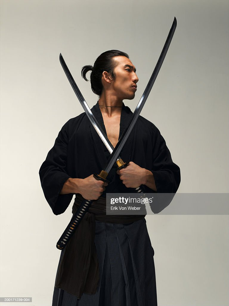 Man holding two swords, looking away : Stock Photo