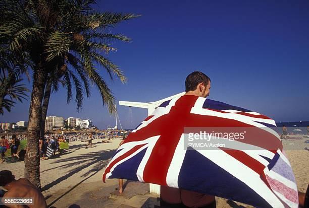 Man holding Union jack beach towel walking along beach Majorca Magaluf 2000s