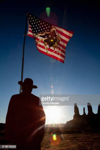 Man holding United States flag with Native American depiction near rock formations, Monument Valley, Utah, United States