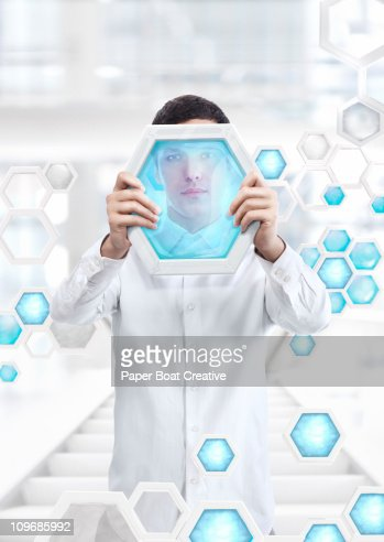 man holding up a blue gel hexagon in a white lab : Bildbanksbilder