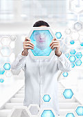man holding up a blue gel hexagon in a white lab
