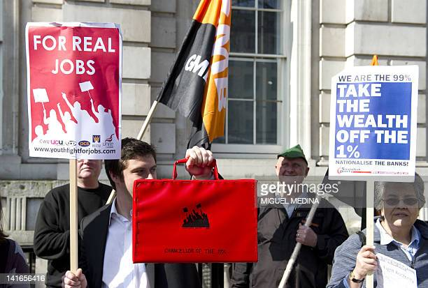 A man holding up a mockup of the Budget Box joins a demonstration in front of Downing street against the budget in central London on March 21 2012...