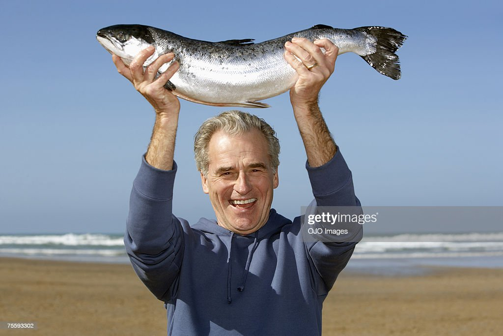 Man holding up a whole fish at the beach : Stock Photo