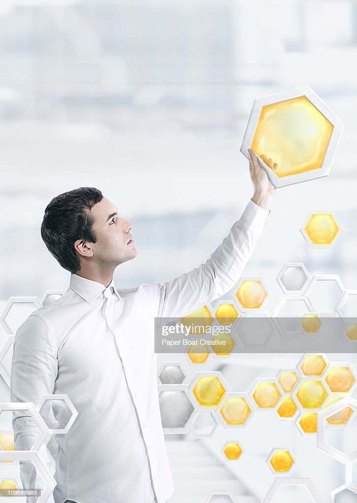 Man holding up a yellow honeycomb model : Stock Photo
