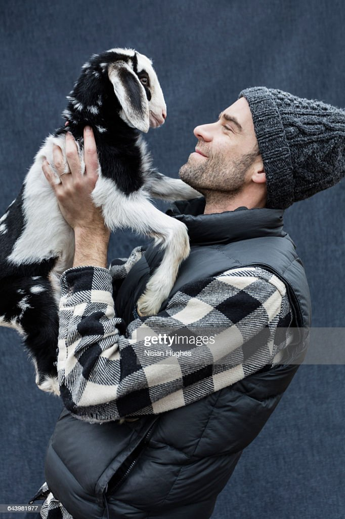 Man holding up baby goat and smilling