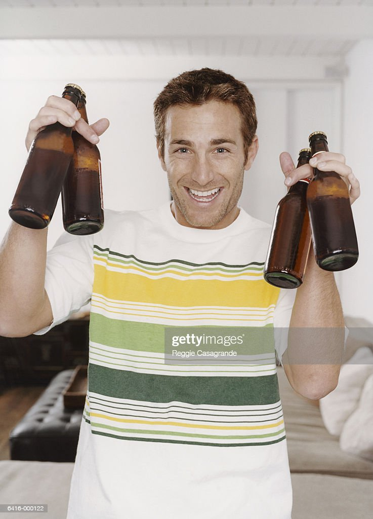 Man Holding Up Beer Bottles : Stock Photo