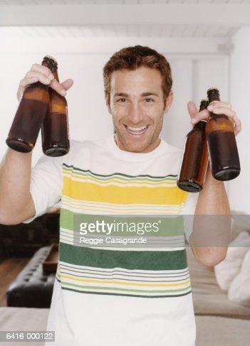 Man Holding Up Beer Bottles : Stock Photo