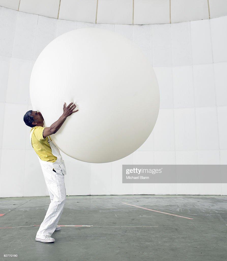 man holding up huge balloon
