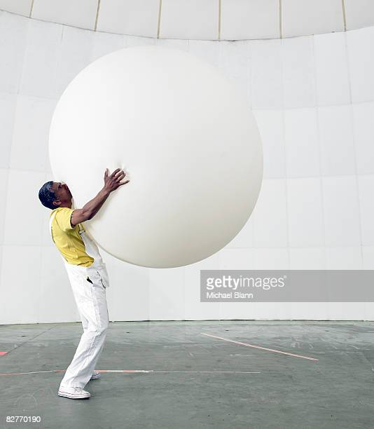 man holding up huge balloon