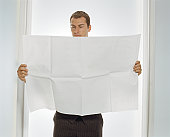 Man holding up large piece of paper