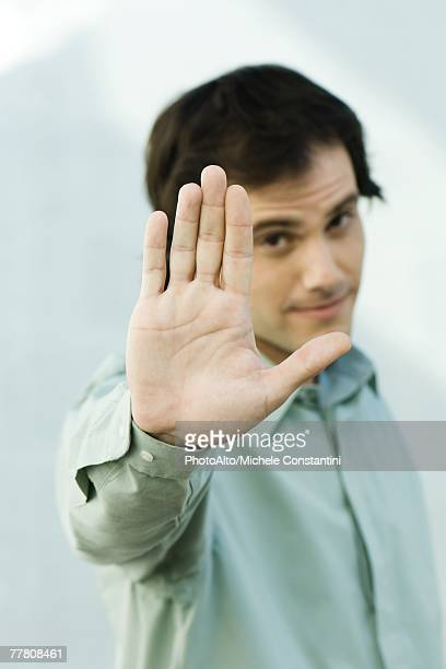 Man holding up palm to camera, portrait