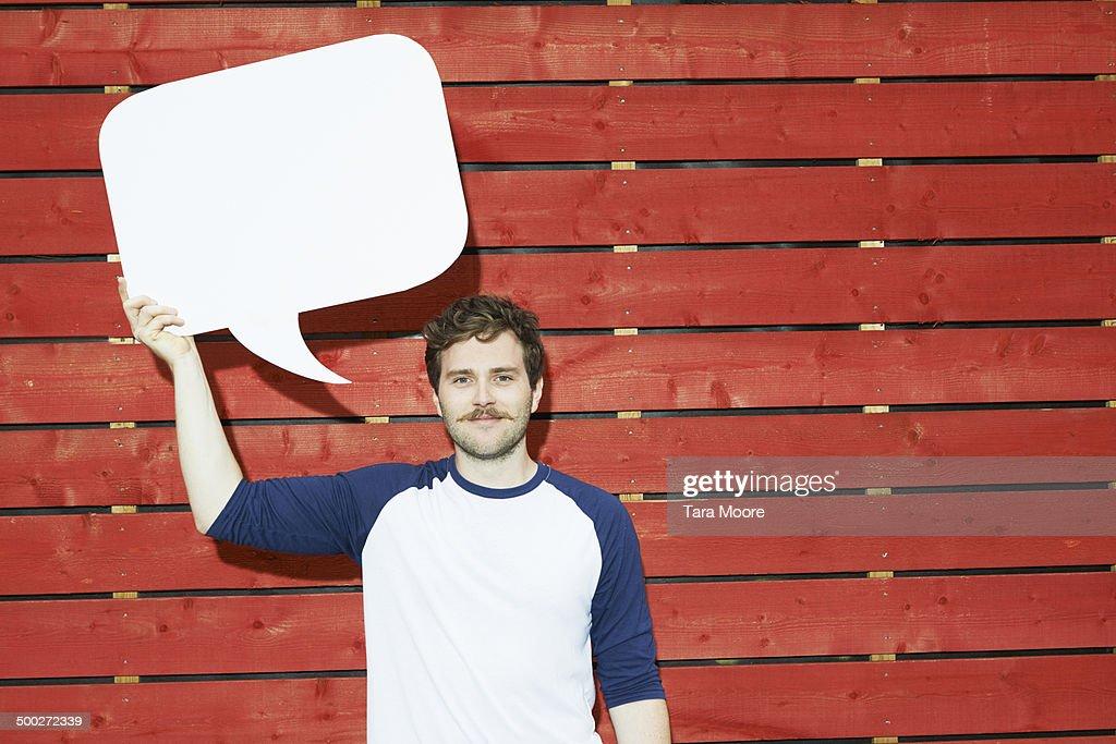man holding up speech bubble