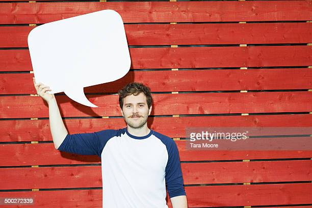 man holding up speech bubble