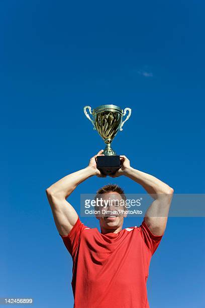 Man holding up trophy cup
