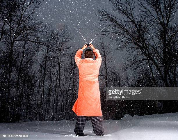 Man holding up  TV antenna during snowstorm, rear view