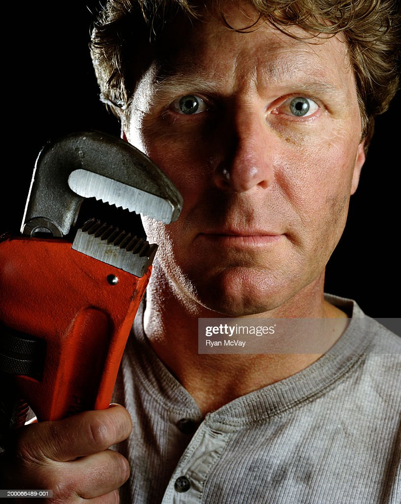 Man holding up wrench, portrait : Stock Photo