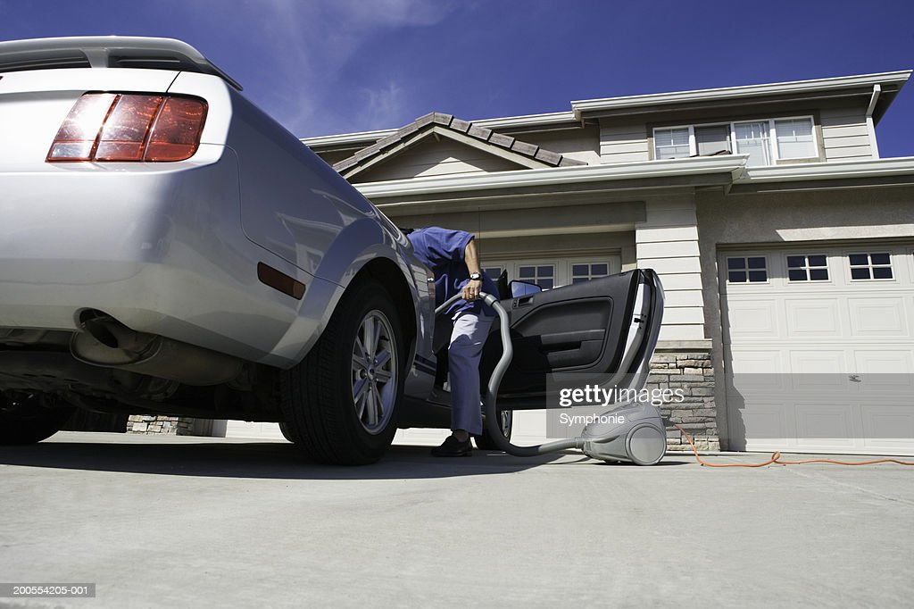 Man holding vacuum cleaner leaning in to car, low angle view : Stock Photo