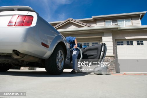 Man holding vacuum cleaner leaning in to car, low angle view : Bildbanksbilder