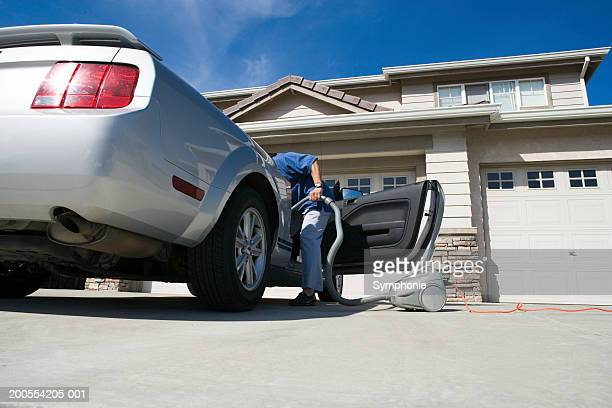 Man holding vacuum cleaner leaning in to car, low angle view