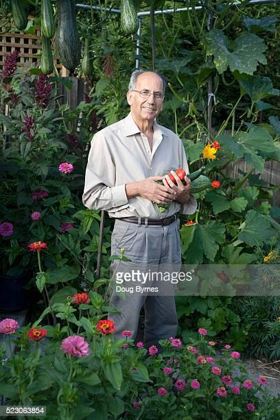 Man holding vegetables in garden